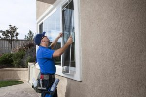 Man cleaning window of a home and installing a screen,